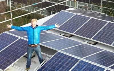 Man standing on roof with solar panels